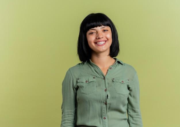 La giovane ragazza caucasica castana sorridente sta isolata su fondo verde oliva con lo spazio della copia
