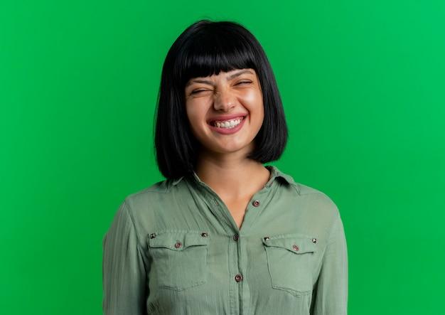 La giovane ragazza caucasica del brunette sorridente sta con gli occhi chiusi isolati su priorità bassa verde con lo spazio della copia