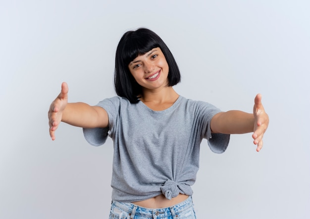 La giovane ragazza caucasica castana sorridente che allunga distribuisce fingendo di tenere qualcosa