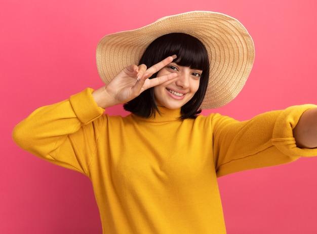 Sorridente giovane ragazza bruna caucasica che indossa il cappello da spiaggia gesti il segno di vittoria prendendo selfie sul rosa