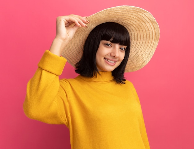 La giovane ragazza caucasica castana sorridente che porta il cappello della spiaggia esamina la macchina fotografica