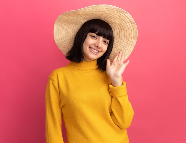 Smiling young brunette caucasian girl wearing beach hat stands with raised hand isolated on pink wall with copy space