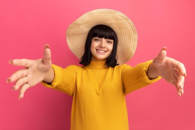 コピースペースでピンクの壁に分離された手を伸ばすビーチ帽子をかぶって若いブルネット白人の女の子の笑顔