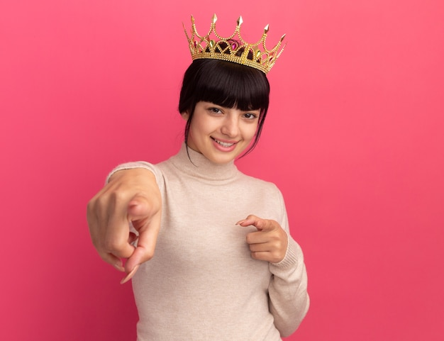 コピースペースとピンクの壁に分離された両手でクラウンポイントを持つ若いブルネット白人の女の子の笑顔