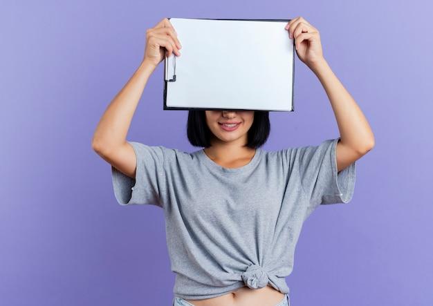 笑顔の若いブルネット白人女性は、コピースペースで紫色の背景に分離されたクリップボードを保持して目を閉じます。