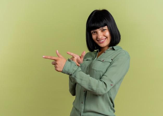 La giovane donna caucasica castana sorridente indica a lato con due mani che esaminano macchina fotografica isolata su fondo verde oliva con lo spazio della copia