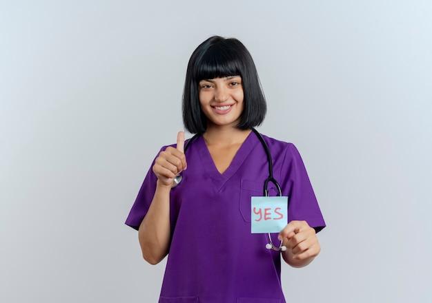 청진 제복을 입은 젊은 갈색 머리 여성 의사 미소 예 참고 및 엄지 손가락 보유
