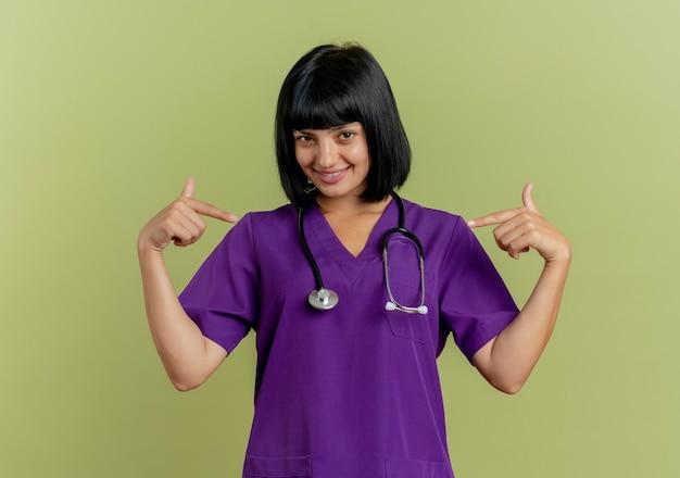 聴診器と制服を着た若いブルネットの女性医師の笑顔は、コピースペースとオリーブグリーンの背景に分離された両手で自分自身を指しています