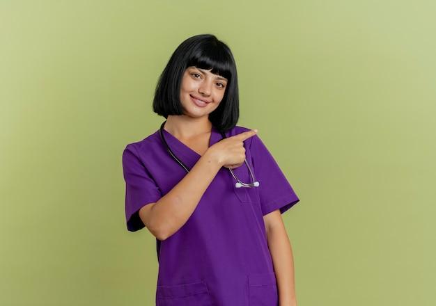 Улыбающаяся молодая брюнетка женщина-врач в униформе со стетоскопом указывает сбоку