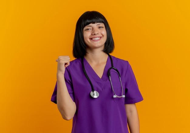 コピースペースとオレンジ色の背景に分離された聴診器ポイントの後ろに制服を着た若いブルネットの女性医師の笑顔