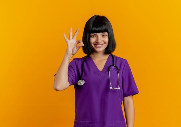 Sorridente giovane dottoressa bruna in uniforme con il segno giusto della mano di gesti dello stetoscopio