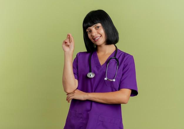 Il giovane medico femminile castana sorridente in uniforme con lo stetoscopio tiene lo sguardo della mano