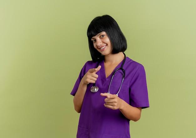 Sorridente giovane donna bruna medico in uniforme con i punti dello stetoscopio dietro con due mani