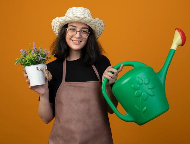Улыбающаяся молодая брюнетка женщина-садовник в оптических очках и в униформе в садовой шляпе держит лейку над цветочным горшком, изолированным на оранжевой стене с копией пространства