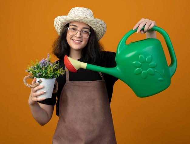 광학 안경에 젊은 갈색 머리 여성 정원사 웃 고 복사 공간 오렌지 벽에 고립 된 화분에 물을 들고 원예 모자를 쓰고 제복을 입은