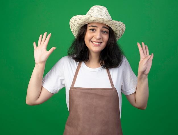 緑の壁に隔離された指でガーデニング帽子のジェスチャー9を身に着けている光学ガラスと制服を着た若いブルネットの女性の庭師の笑顔