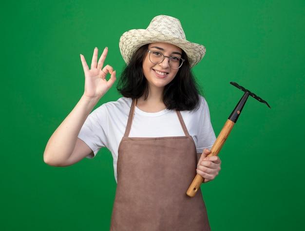 光学ガラスと制服を着た若いブルネットの女性の庭師の笑顔は、ガーデニング帽子のジェスチャーでokハンドサインを着て、緑の壁に分離された熊手を保持します