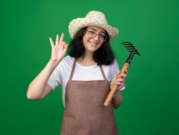 光学ガラスと制服を着た若いブルネットの女性の庭師の笑顔は、okの手のサインを身振りで示すガーデニング帽子を身に着けて、緑の壁に分離された熊手を保持します
