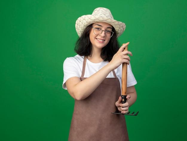 광학 안경에 웃는 젊은 갈색 머리 여성 정원사 및 원예 모자를 쓰고 제복은 녹색 벽에 고립 된 갈퀴를 거꾸로 보유