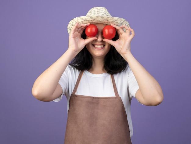 원예 모자를 쓰고 제복을 입은 젊은 갈색 머리 여성 정원사 미소는 보라색 벽에 고립 된 토마토로 눈을 덮습니다.