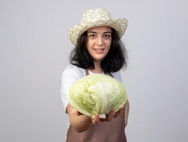 Улыбающаяся молодая брюнетка женщина-садовник в униформе в садовой шляпе держит капусту, изолированную на белой стене