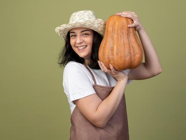 Улыбающаяся молодая брюнетка женщина-садовник в униформе в садовой шляпе держит тыкву, изолированную на оливково-зеленой стене