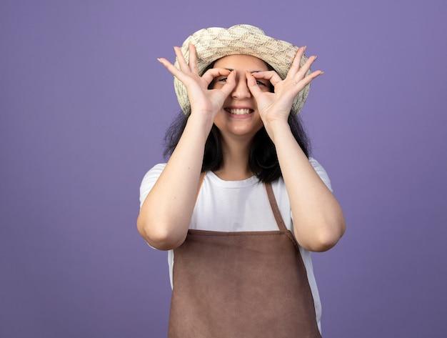 ガーデニング帽子をかぶって制服を着た若いブルネットの女性の庭師の笑顔は紫色の壁に分離された指を通して正面を見る