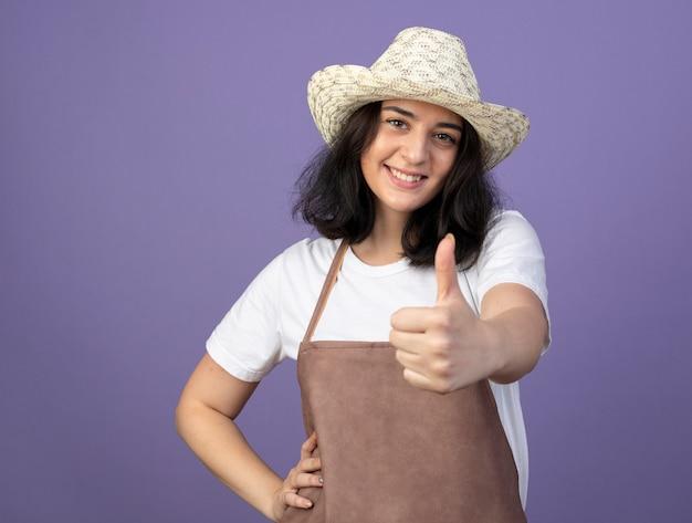 紫色の壁に分離された園芸帽子の親指を身に着けている制服を着た若いブルネットの女性の庭師の笑顔