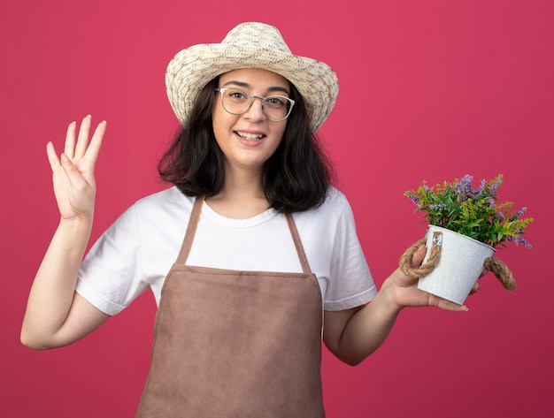 Smiling young brunette female gardener in optical glasses and in uniform wearing gardening hat holds flowerpot and gestures four with fingers isolated on pink wall with copy space