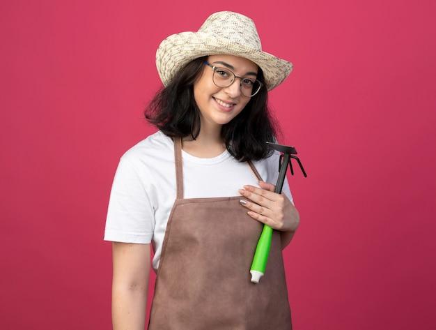 Il giovane giardiniere femminile castana sorridente in vetri ottici e in uniforme che porta il cappello di giardinaggio tiene il rastrello della zappa isolato sulla parete rosa