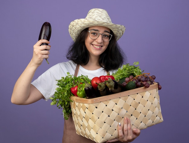Il giovane giardiniere femminile castana sorridente in vetri ottici e in uniforme che porta il cappello da giardinaggio tiene il cestino e la melanzana della verdura isolati sulla parete viola