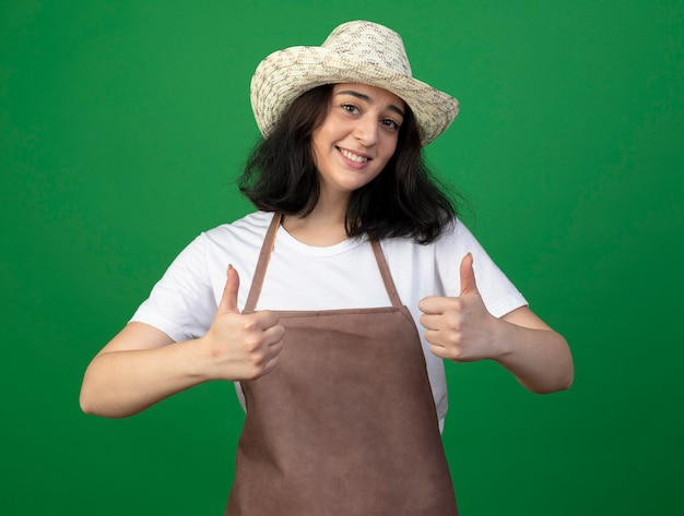 Smiling young brunette female gardener in optical glasses and uniform wearing gardening hat thumbs up of two hands isolated on green wall