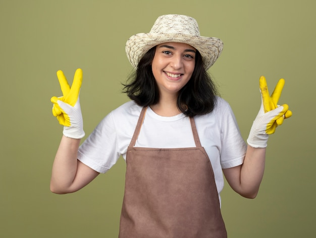 Smiling young brunette female gardener in uniform wearing gardening hat and gloves gestures victory hand sign with two hands isolated on olive green wall
