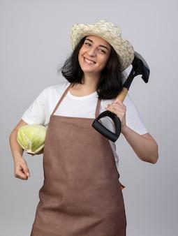 Il giovane giardiniere femminile castana sorridente in cappello da giardinaggio d'uso uniforme tiene il cavolo e la vanga sulla spalla isolata sulla parete bianca
