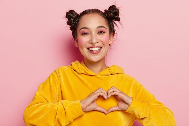 Smiling young brunette girl confesses true feelings, makes heart gesture, dressed in yellow hoody, shows heart gesture