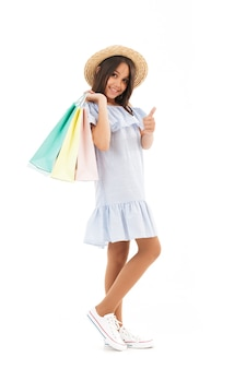 Smiling young brunette girl in dress and straw hat holding packages while looking at the camera and showing thumb up on white