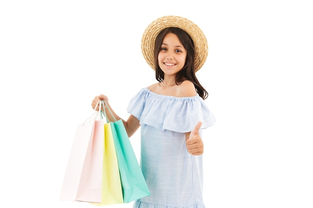Smiling young brunette girl in dress and straw hat holding packages while showing thumb up on white
