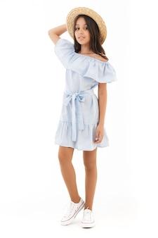 Улыбающаяся молодая брюнетка в платье и соломенной шляпе позирует на белом