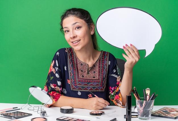 吹き出しを保持している化粧ツールとテーブルに座っている若いブルネットの少女の笑顔