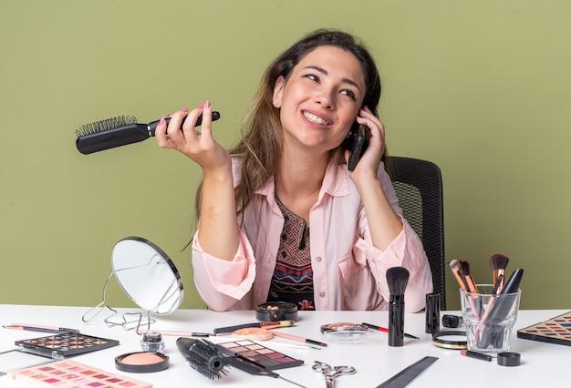 Улыбающаяся молодая брюнетка девушка сидит за столом с инструментами для макияжа, разговаривает по телефону и держит расческу, изолированную на оливково-зеленой стене с копией пространства
