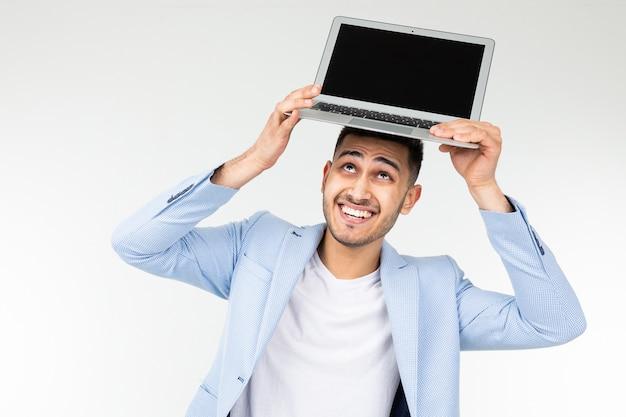 흰색 배경에 빈 모형 카메라에 노트북 화면을 들고 웃는 젊은 갈색 머리 남자