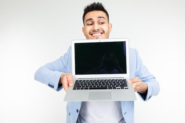 Улыбающийся молодой человек брюнетки, держащий экран ноутбука перед камерой с пустым макетом на белом фоне.