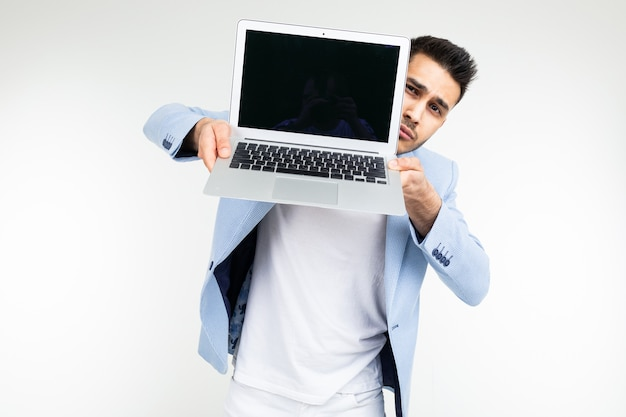 Smiling young brunette man holding a laptop screen to the camera with a blank mockup on a white background
