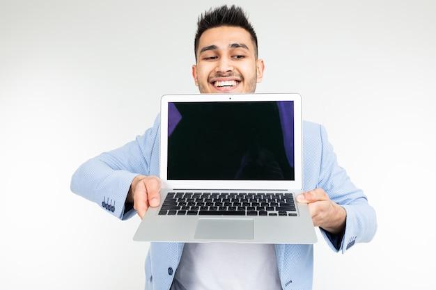 Улыбающийся молодой человек брюнетки радостно держит ноутбук с пробелом для вставки страницы веб-сайта на белом фоне.