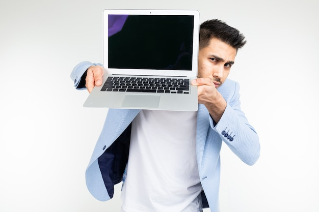 Smiling young brunette man joyfully holds a laptop with blank for inserting a website page on a white background