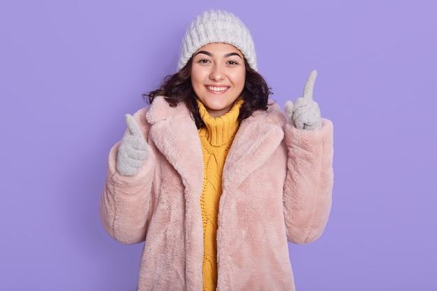 笑顔の若いブルネットの女性は、黄色のセーター、ピンクのフェイクファーのコートとキャップを着て、ライラックの背景に孤立したポーズをとり、指を上に向けてカメラに向けます。
