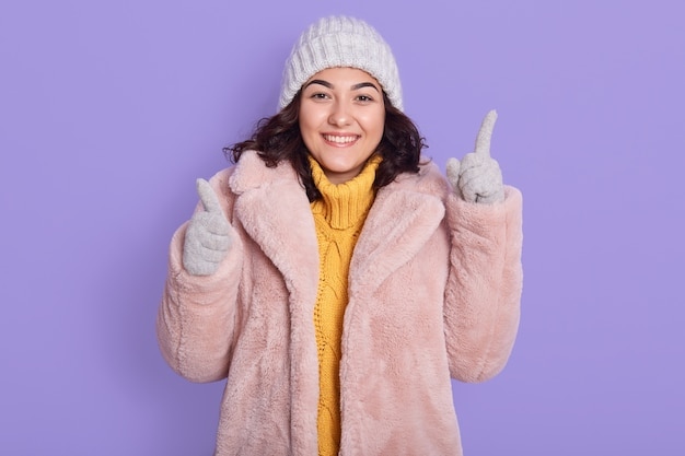Smiling young brunette woman dresses in yellow sweater, pink faux fur coat and cap, posing isolated on lilac background, pointing fingers up and to camera.