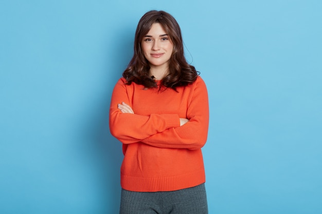 Smiling young brunette woman girl in sweater posing blue