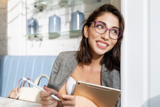 Smiling young brunette woman in glasses with a tablet sits in a cafe and looks out the window. online business and distance learning.