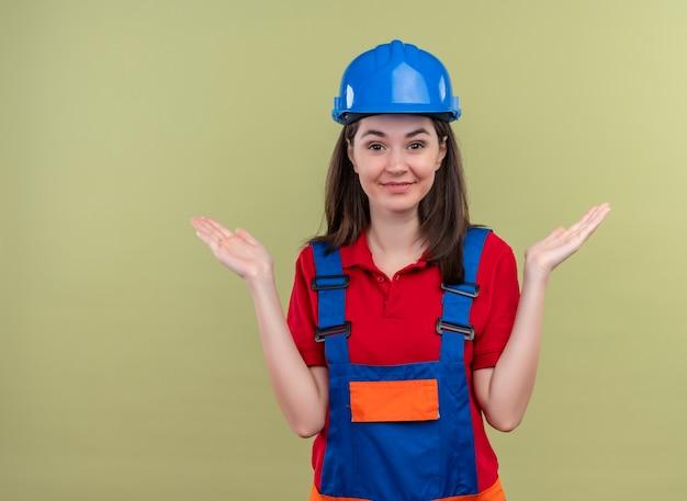 Улыбающаяся молодая девушка-строитель в синем защитном шлеме держит руку на изолированном зеленом фоне с копией пространства